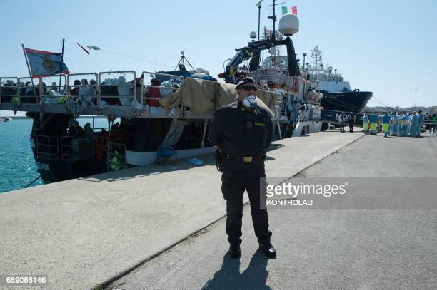 A policeman during the phase of landing migrants from Phoenix MOAS ship in the port of Crotone Calabria southern Italy 600 refugees landed from...