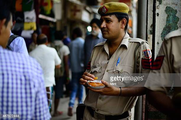 A policeman eats jalebi at the old famous Jalebi wala at the corner of Dariba in Chandni Chowk on August 20 2014 in New Delhi India Chandni Chowk...