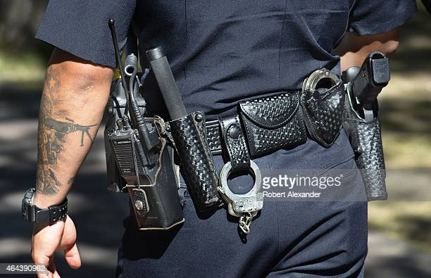 A policeman equipped with a Glock revolver handcuffs and a radio on his belt patrols a street in Santa Fe New Mexico On his arm is a patriotic...
