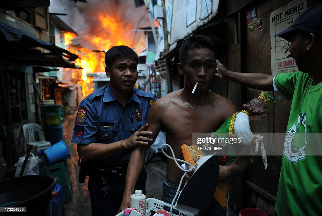 A policeman (L) escorts a resident (C) carrying salvaged belongings from his burning house as a fire engulfs a shanty town in the financial district of Manila on July 11, 2013, leaving more than 1,000 people homeless according to city officials. There were no immediate reports of casualties from the blaze, which occurred mid-morning amid government plans to relocate thousands of families living in areas vulnerable to floods and typhoons.