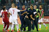 A policeman escorts a Serbian fan that invaded the pitch after a flag with Albanian national symbols was flown by a remotely operated drone during...