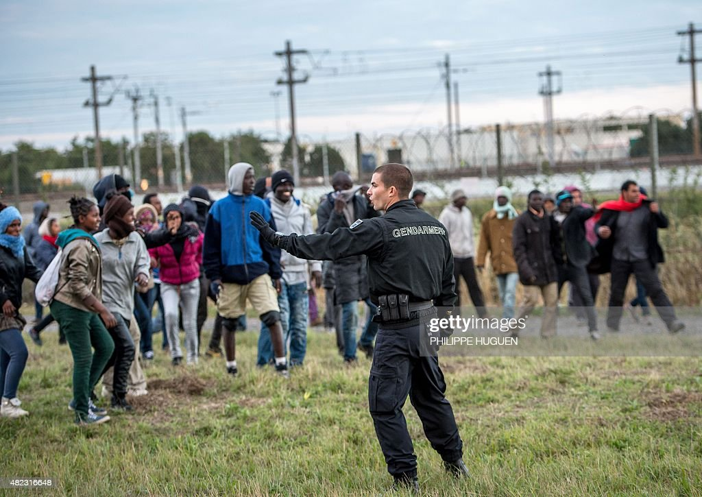 A policeman faces migrants trying to reach the Channel Tunnel operated by Eurotunnel in Coquelles near Calais northern France on late July 29 2015...
