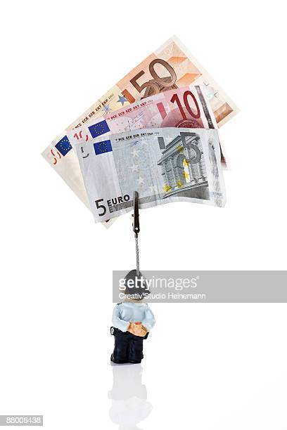Policeman figurine holding Euro notes, rear view