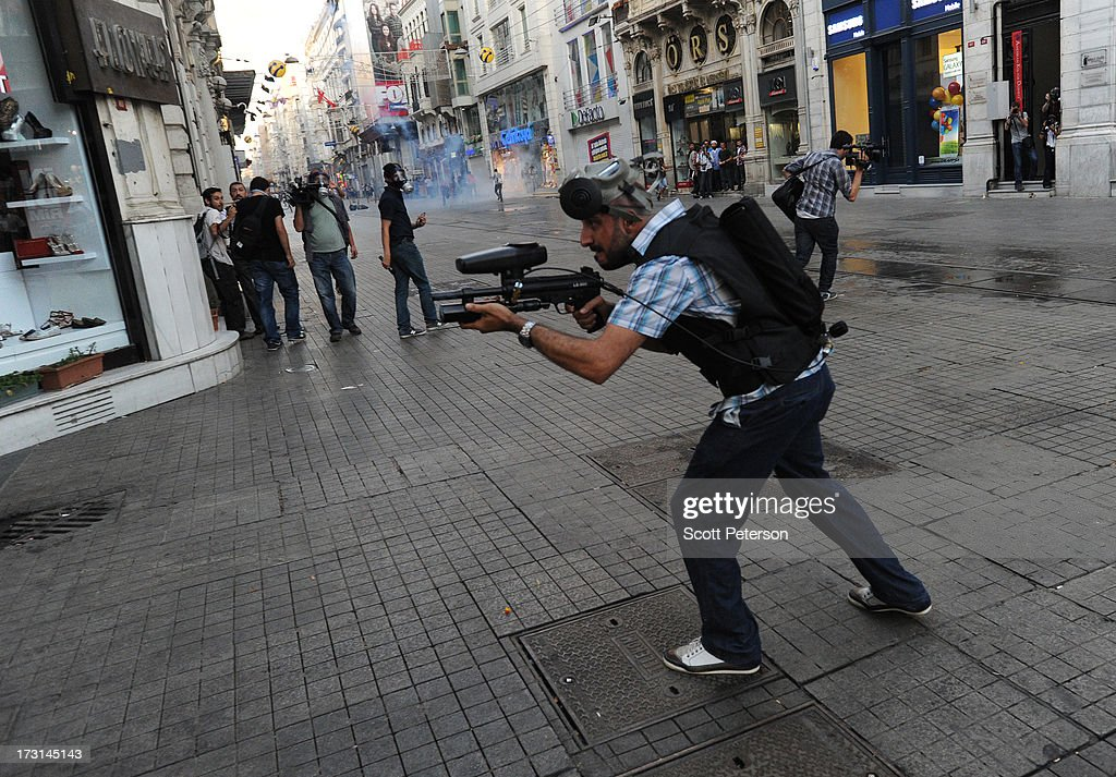 A policeman fires paintballs as Turkish police battle anti-government protestors along the Istiklal shopping street near Taksim Square on July 8, 2013 in Istanbul, Turkey. The protests began in late May over the Gezi Park redevelopment project and saving the park trees adjacent to Taksim Square but swiftly turned into a protest aimed at Prime Minister Recep Tayyip Erdogan and what protestors call his increasingly authoritarian rule. The protest spread to dozens of cities in Turkey, in secular anger against Mr. Erdogan and his Islam-rooted Justice and Development Party (AKP).