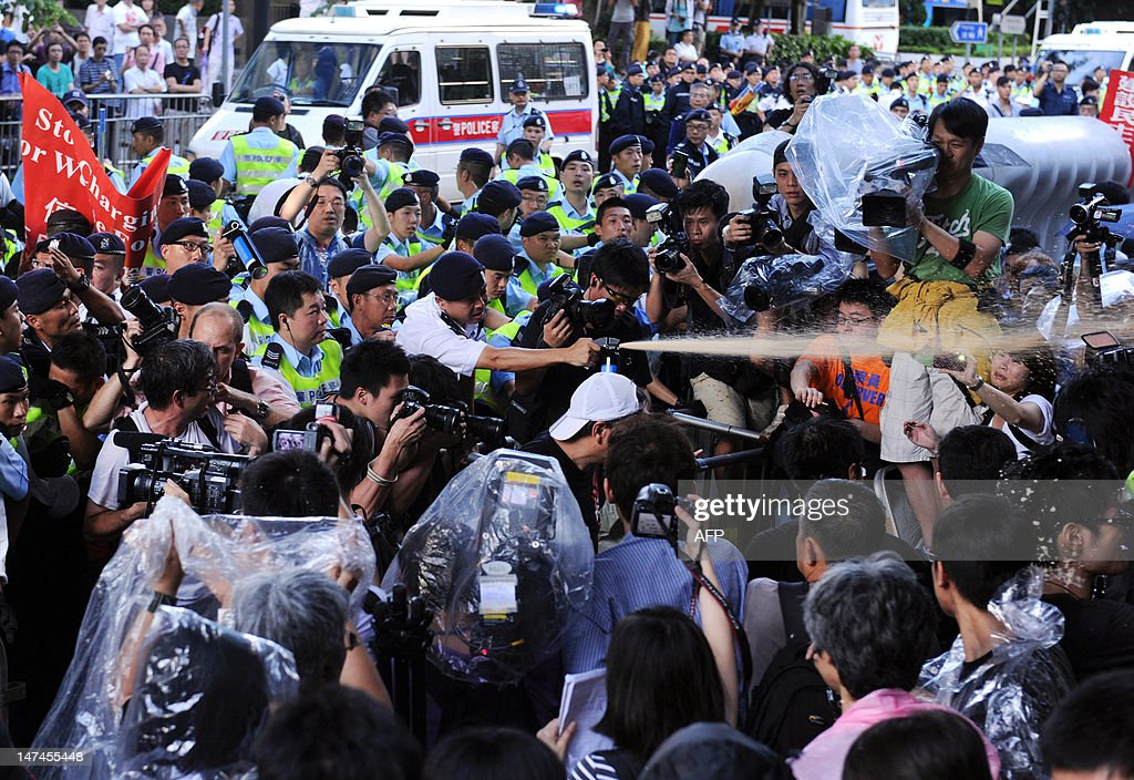 A policeman fires pepper spray towards prodemocracy demonstrators calling on the Chinese government to investigate the death of dissident Li Wangyang...