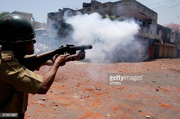 A policeman fires teargas during violence in the streets of the western city of Vadodara 01 May 2006 Two people were killed when mobs of Hindus and...