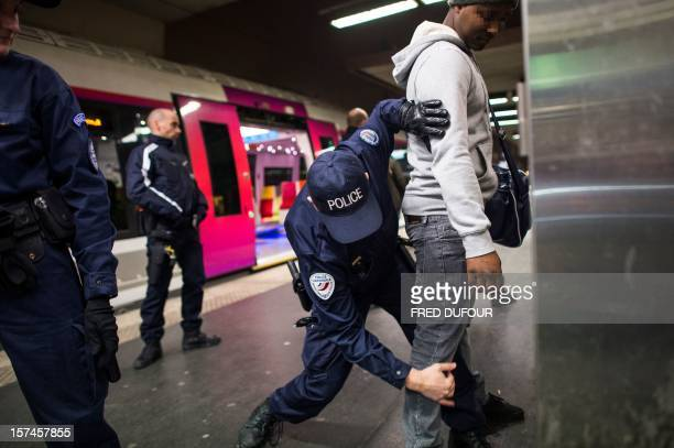 A policeman frisks a man as he searches his belongings during a patrol of the Gare du Nord in Paris on November 30 2012 AFP PHOTO / FRED DUFOUR