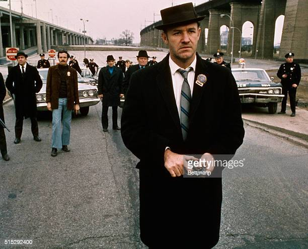 Policeman Gene Hackman is shown in this movie still walking toward the camera He is holding a gun in his hands with policemen and police vehicles in...