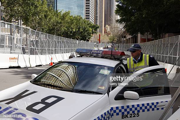 A policeman gets into a police car parked between security fences on September 6 2007 in Sydney Australia Fences have been erected in many areas of...