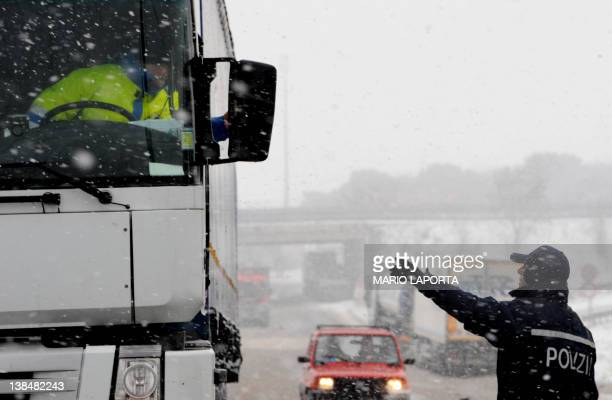 A policeman gives information to a truck driver during a snowfall at a highway exit near Candela on Februery 7 2012 Many highways are closed in the...
