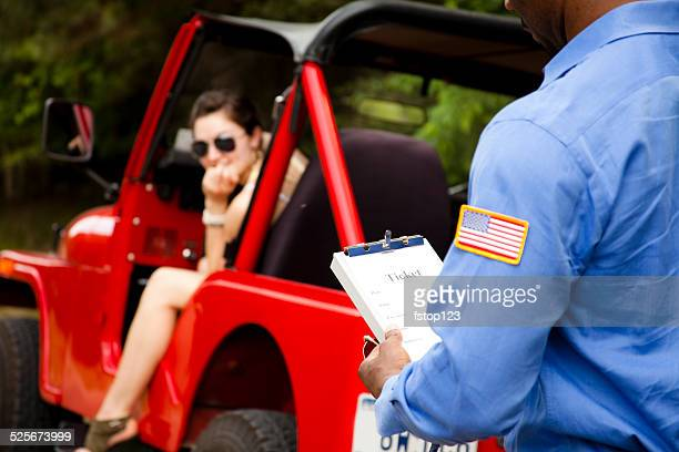Policeman gives woman driver a traffic ticket for speeding. Vehicle.