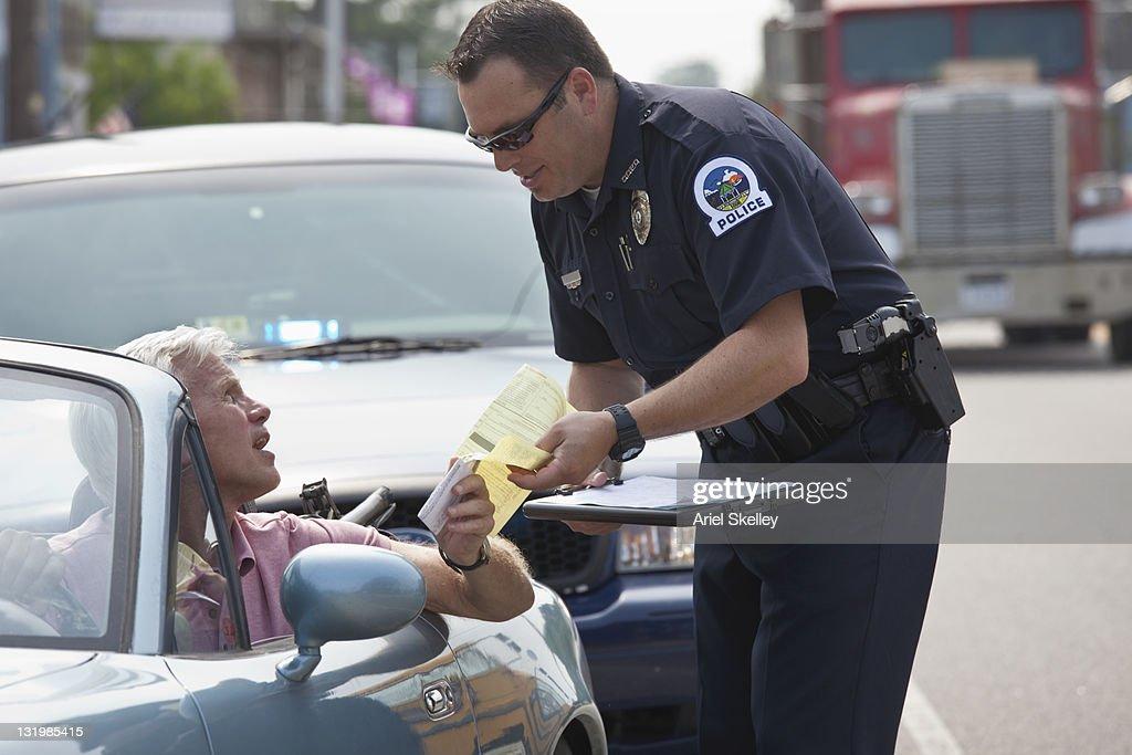 Policeman giving driver traffic citation : Stock Photo