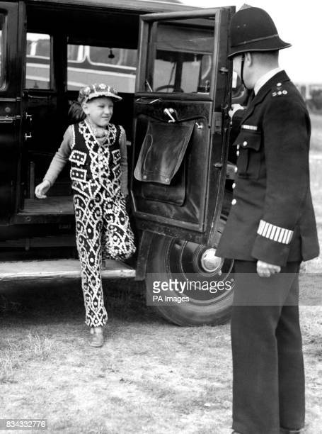 A policeman greets Master Cifford Marriott son of the Coster King and Queen of London and Finsbury on his arrival at Epsom