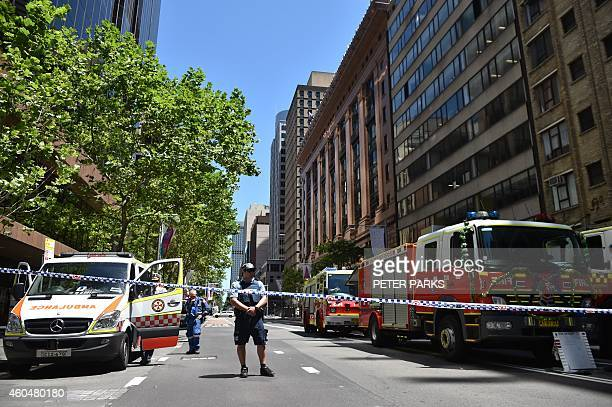 A policeman guards a road leading to a cafe in the central business district of Sydney on December 15 2014 A gunman was holding terrified hostages...