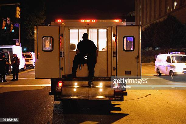 A policeman guards arrested youths in the back of a police van after being arrested by riot police near the campus of the University of Pittsburgh...