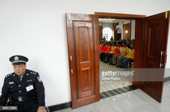 A policeman guards the court room as 19 gang members listen to their sentence during a trial at the Meishan Intermediate People's Court on October 12...