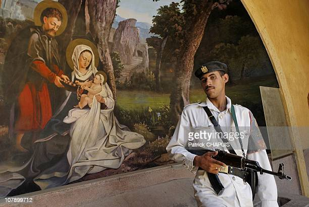 A policeman guards the historical site of the Virgin Mary's Tree in Mataria in front of a painting showing the Holy Family visit during exile in...