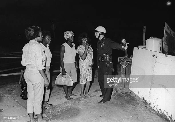 A policeman guides a group of women to safety during rioting in the Watts area of Los Angeles August 1965 Their homes have been destroyed during the...