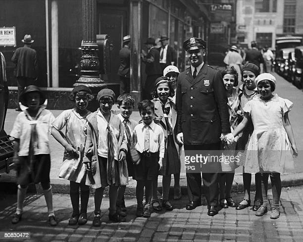 A policeman helps a group of children across the street New York circa 1930
