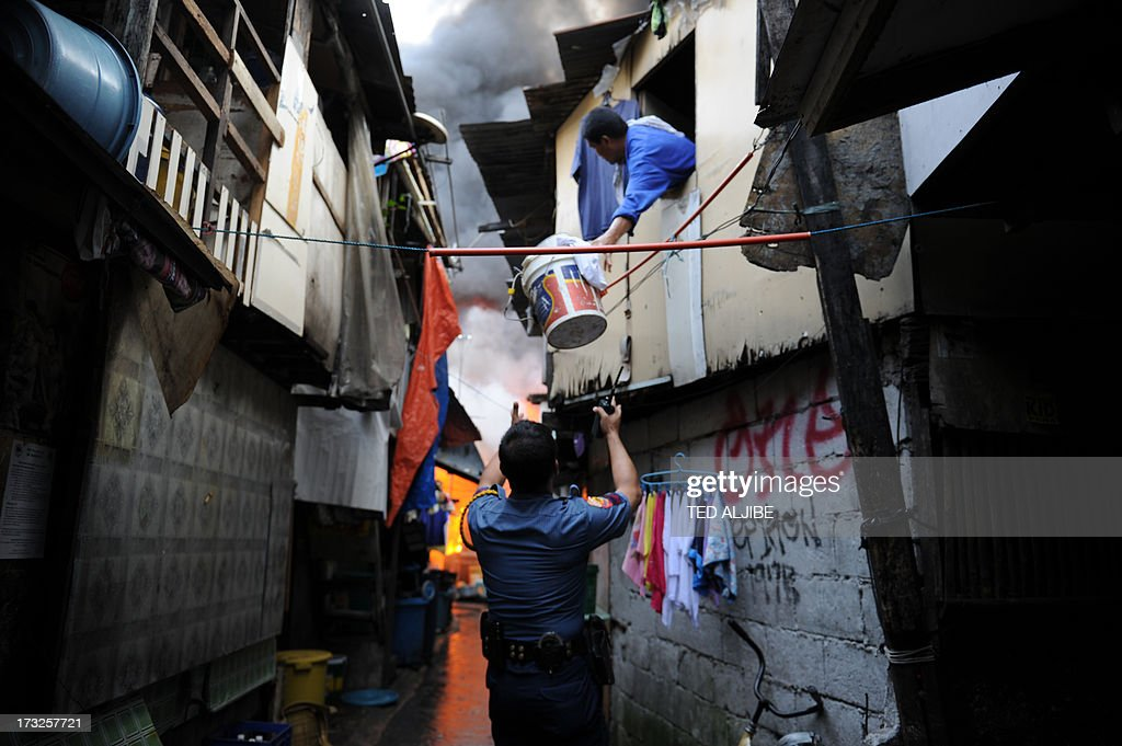 A policeman helps a resident to evacuate from burning houses after a fire engulfed a shanty town at the financial district of Manila on July 11, 2013. There were no immediate reports of casualties from the blaze, which occurred mid-morning amid government plans to relocate thousands of families living in areas vulnerable to floods and typhoons.
