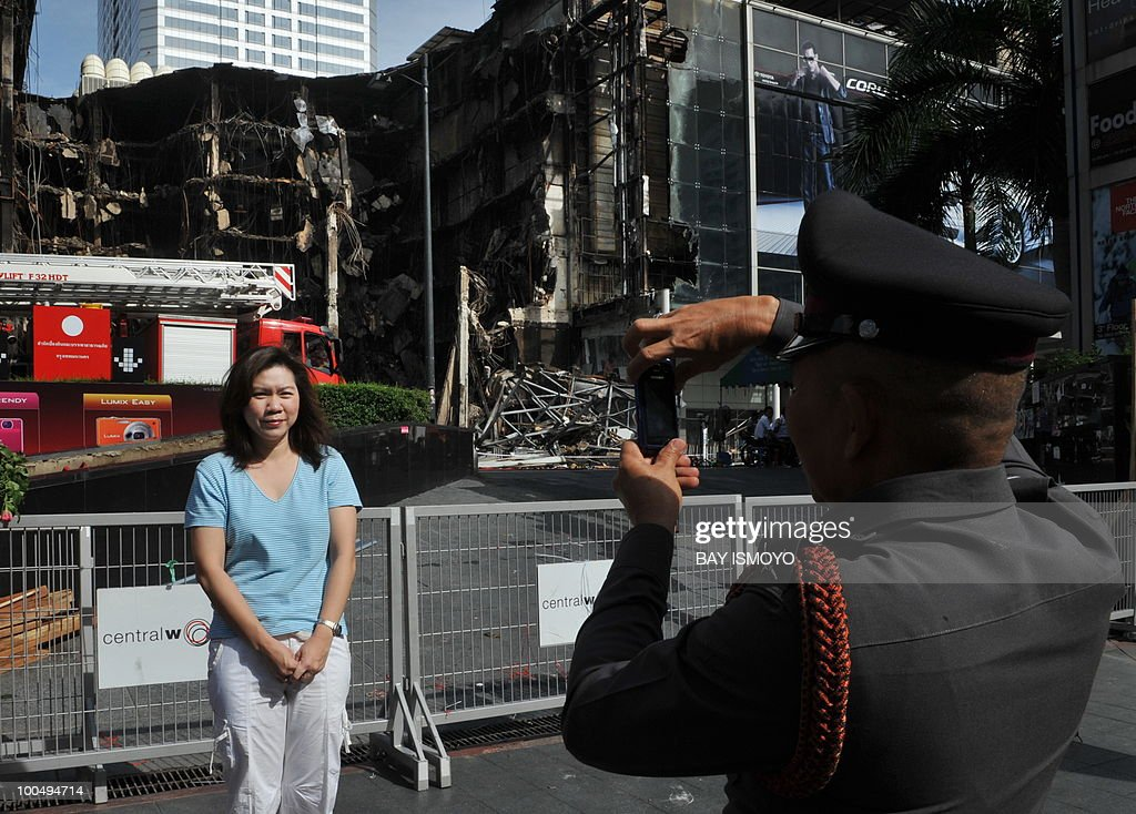 A policeman helps a woman to take her picture in front of a collapsed Central World shopping mall in downtown Bangkok on May 25, 2010 following recent anti-government protest. Thai authorities will ask the government to extend a curfew in Bangkok and 23 provinces for another week in the wake of a crackdown on anti-government protesters, an army official said. AFP PHOTO / Bay ISMOYO