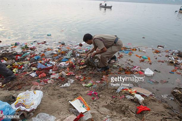 A policeman helps in cleaning the garbage dumped at the river bank of Yamuna during the 'Swachh Bharat Abhiyan' or Clean India Mission early in the...