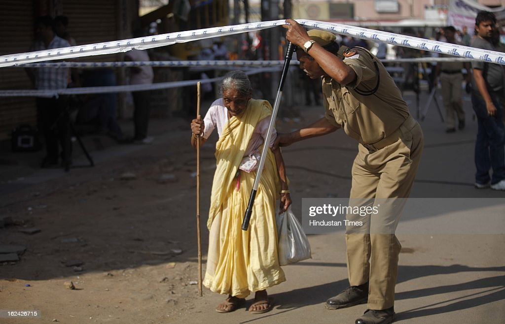 A policeman helps to an old woman at one of the sites of dual bomb blast on February 23, 2013 in Hyderabad, India. The dual blast which occurred on Thursday, reportedly killed 16 people.