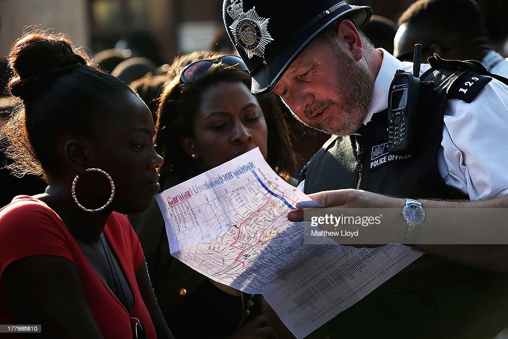 A policeman helps with directions during the Notting Hill Carnival on August 26, 2013 in London, England. More than one million people are expected to enjoy this year's Notting Hill Carnival. It is the largest street festival in Europe and was first held in 1964 by the Afro-Caribbean community. Over the bank holiday weekend the streets come alive to steel bands, colourful floats and costumed performers as members of the public flood into the area to join in the celebrations.