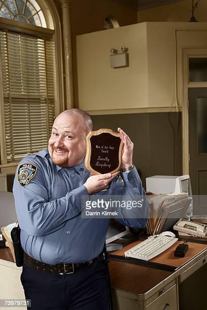 Policeman holding award, smiling, portrait