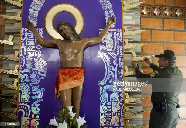 A policeman holds a fiberglass gun part of the work Cristo Moreno by Peruvian artist Cristina Planas Toledo during the opening of the first mausoleum...
