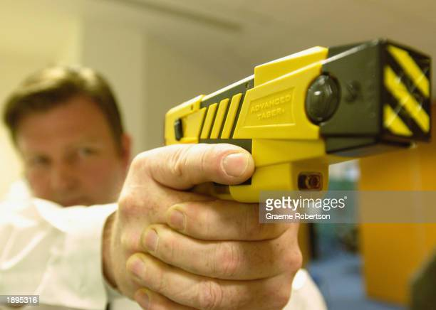 A policeman holds the new advanced taser gun April 4 2003 as the Metropolitan police introduced the Taser gun to the press in London The Metropolitan...
