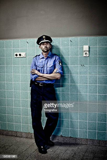 policeman in blue uniform leans against a tiled wall
