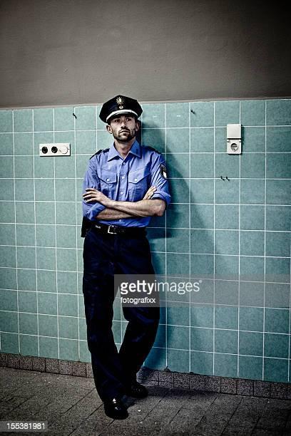 Polizisten in blauer uniform lehnt sich gegen einen gefliesten Wand
