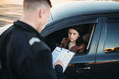Policeman in uniform writes a fine to female driver. Law protection, car traffic inspector, safety control job