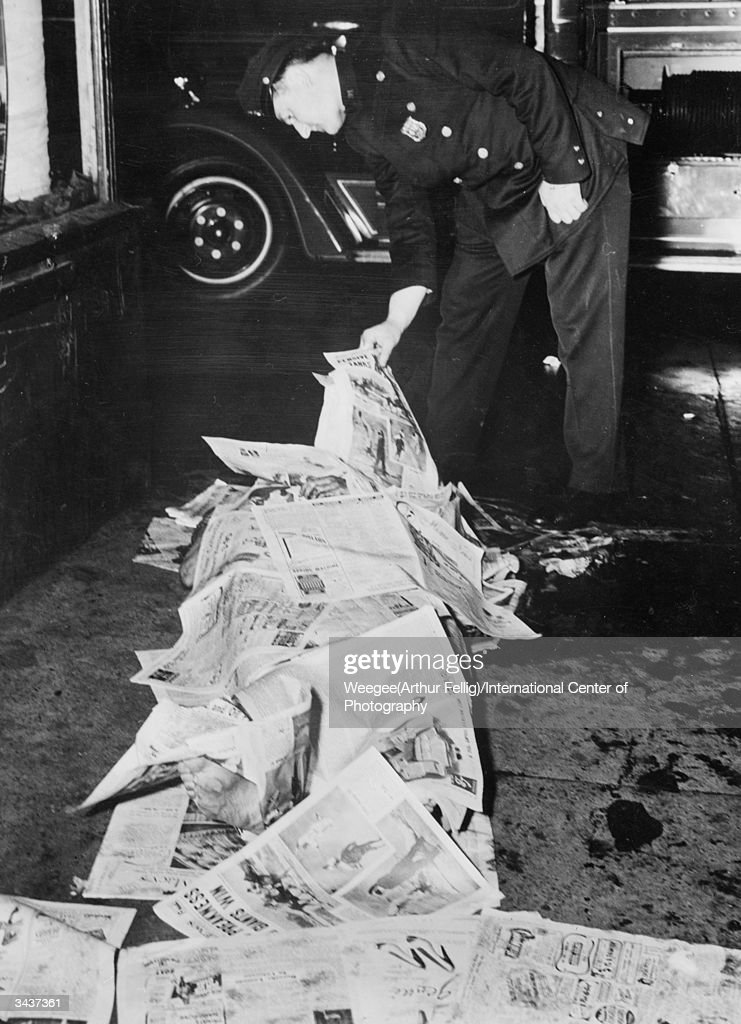 A policeman inspects the body of a murder victim covered with newspaper in New York City. (Photo by Weegee(Arthur Fellig)/International Center of Photography/Getty Images)