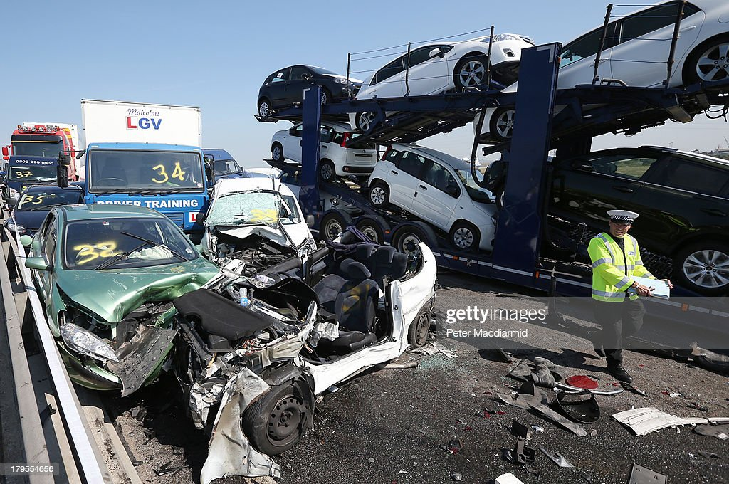 A policeman inspects the site of a major traffic accident on the A249 Sheppey crossing bridge in Kent on September 5, 2013 in Isle of Sheppey, Kent. Over 130 vehicles were involved in the series of accidents, with thick fog blamed for poor visibility. The crash occurred around 07:15AM BST, with at least 8 people suffering serious injuries, and approximately 60 people treated for minor injuries.