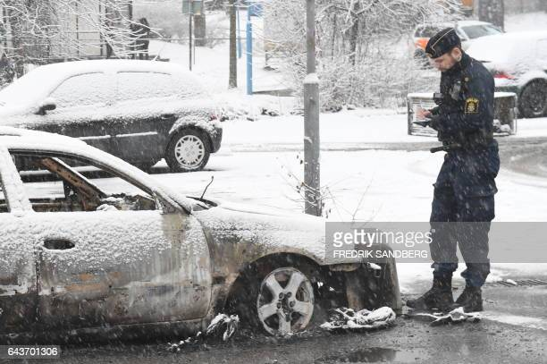 A policeman investigates a burned out car in the suburb Rinkeby outside Stockholm on February 21 2017 Several cars was set in to fire after a riot in...