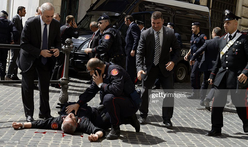 A policeman is helped after being shot by an apparently disturbed man, on April 28, 2013 in Rome, outside the palazzo Chigi, the Italian Prime minister offices, while the country's new ministers were being sworn in. Two policemen were wounded, as well as a passerby, in the shooting. The attacker, named by Italian media as businessman Luigi Preiti, 49, was tackled to the ground by by police as witnesses fled the scene.