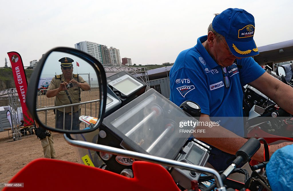 A policeman is reflected on the mirror of a motorcycle as he takes a picture in Lima on January 3, 2013, ahead of the 2013 Dakar Rally which this year will thunder through Peru, Argentina and Chile from January 5 to 20.