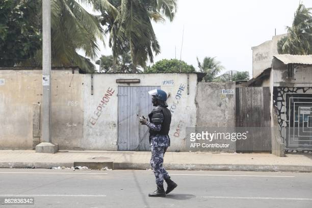 A policeman is seen observing protesters after opposition supporters have erected makeshift barricades and block roads in Lome on October 18 2017...