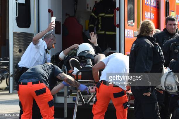 A policeman is taken into an ambulance during clashes with protesters July 7 2017 in Hamburg northern Germany where leaders of the world's top...
