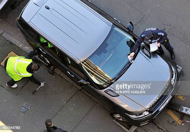 A policeman issues on December 18 2013 a parking ticket on a car which was parked in front of a garage in Lille while a car pound employee prepares...
