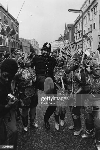A policeman joins in the fun of the 1978 Notting Hill Carnival dancing and highkicking down the road with some fellow revellers