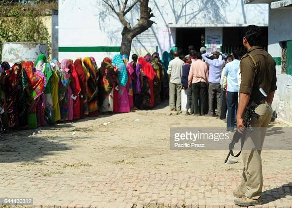 A policeman keep vigil as people stand in queue to cast their votes for the 4th phase of assembly election in Allahabad