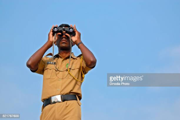 Policeman keeping watch through binocular