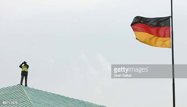 A policeman keeps watch from the roof of a building opposite the Neue Wache war memorial while a German flag blows at half mast before the arrival of...