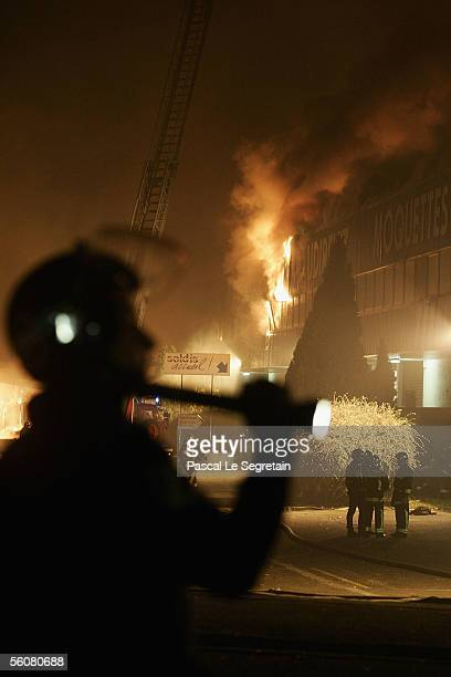 A policeman keeps watch over a warehouse set ablaze in the early hours on November 4 2005 in AulnaysousBois outside Paris France French authorities...