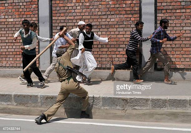 Policeman lathi charge on Kashmiri daily wage government employee during a protest rally on May 7 2015 in Srinagar India Dozens of government...