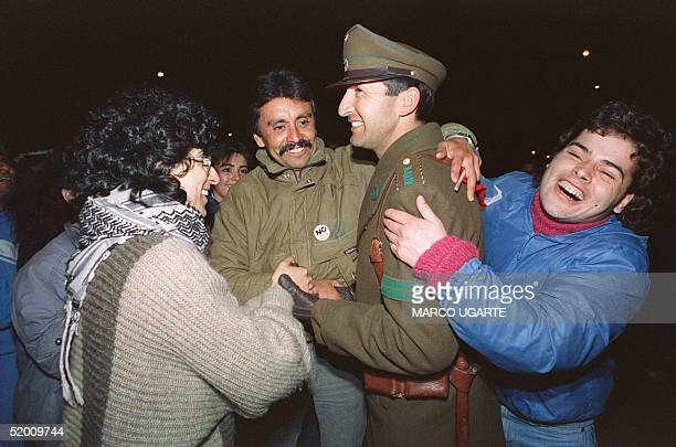 A policeman laughs 06 October 1988 in Santiago with a group of Chileans celebrating the victory of the 'No' faction in the 05 October plebiscite...