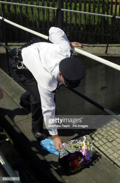 A policeman lays flowers at Tottenham Lock on the River Lea in Tottenham north London where police looking for Andrea Auriglietti recovered a body of...